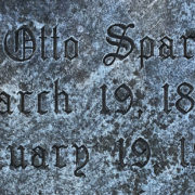 Old English SR lettering on a cemetery headstone.